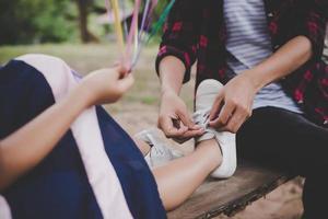 mãe amarra sapato para a filha enquanto está sentada no balanço