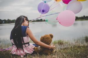 menina com um ursinho de pelúcia e balões no campo foto