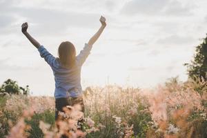 bela jovem estende os braços no ar em um campo foto
