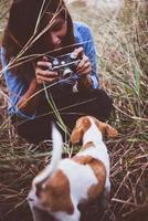mulher hipster tirando uma foto de seu cachorro com sua câmera vintage