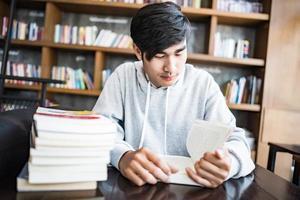jovem lendo livros em um café foto