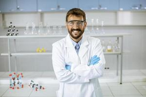 jovem cientista com jaleco branco em pé no laboratório biomédico foto
