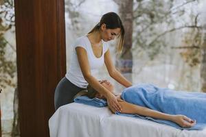 bela jovem deitada e fazendo massagem nos ombros no salão spa durante o inverno foto