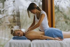 bela jovem deitada e fazendo massagem no pescoço em salão de spa durante o inverno foto