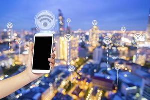 feche a mão segurando o telefone com o ícone de wi-fi foto