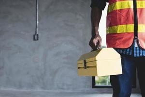 trabalhador segurando caixa de construção foto
