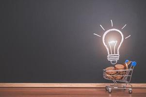carrinho de compras com moedas e desenho de lâmpada