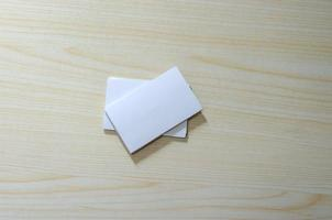 uma maquete de papel em branco para cartões de visita em uma mesa de madeira