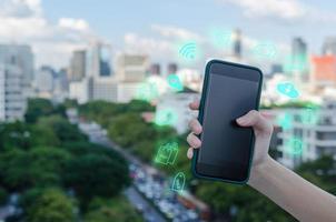 uma mão segurando um smartphone com conceito de ícones no fundo desfocado da cidade