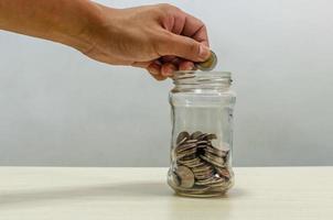 uma mão segurando uma moeda em uma jarra de vidro