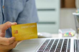 a mão de um homem segurando um cartão de crédito para transações ou compras online foto