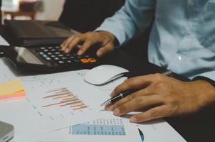 um empresário segurando uma caneta e calculadora para ver gráficos e relatórios de vendas para o crescimento dos negócios