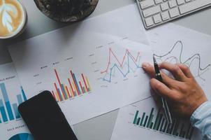a mão de um empresário segurando uma caneta sobre documentos de negócios, gráficos, relatórios e investimentos em uma mesa cinza, telefone celular, café e teclado de computador.