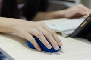 a mão de uma garota segurando um mouse azul de computador