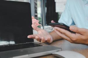 um empresário usando um smartphone móvel e um laptop em uma mesa pesquisando na internet foto
