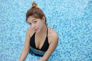 foto de moda de uma linda garota sexy de biquíni preto em uma piscina