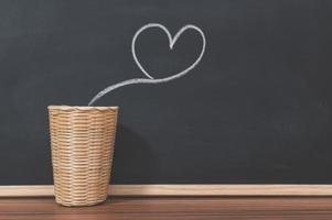 uma chaleira e um formato de coração em um quadro negro foto
