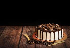 bolo de chocolate com grãos de café na mesa de madeira foto