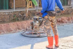 trabalhador da construção civil terminando o concreto úmido com uma ferramenta especial