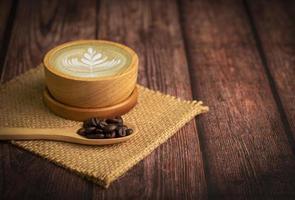 xícara de café e latte art com grãos de café em colher na mesa de madeira