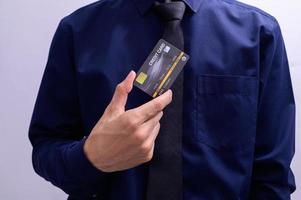 empresário segurando um cartão de crédito