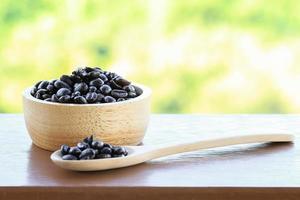 grãos de café em uma tigela de madeira e uma colher de pau na mesa com fundo borrado da natureza