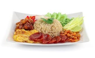 arroz temperado com pasta de camarão e cebola roxa, feijão, manga e ovo frito em prato branco com fundo branco