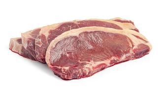 quatro bifes de carne crua no fundo branco foto
