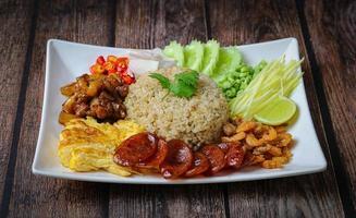 arroz temperado com pasta de camarão, com cebola roxa, feijão, manga e ovo frito na chapa branca na mesa de madeira