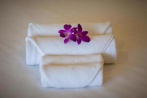 toalhas brancas na cama com flores roxas