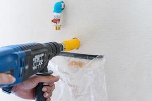 trabalhador usando uma ferramenta de perfuração em canteiro de obras