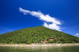 nuvens brancas e céu azul acima de uma montanha