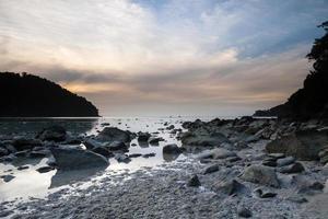 pôr do sol nublado em uma costa rochosa foto