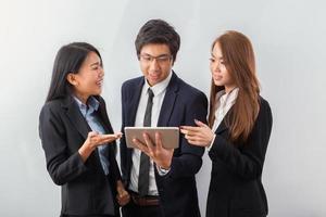 três colegas de trabalho olhando para um tablet