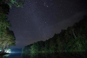 céu estrelado acima da água e árvores à noite foto