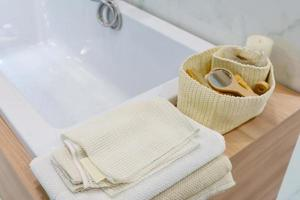 sabonete de cerâmica, frascos de shampoo e toalhas de algodão branco foto