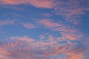nuvens rosa em um céu azul foto