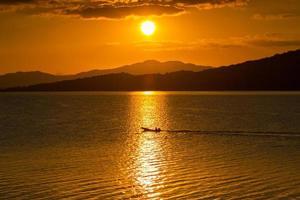 silhuetas de montanha e água ao pôr do sol