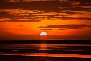 pôr do sol vermelho na praia foto