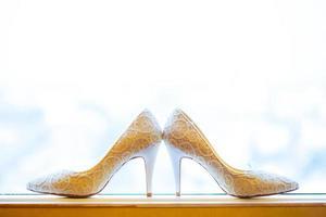sapatos de noiva em uma janela foto
