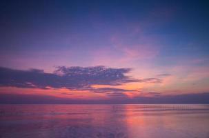 pôr do sol rosa e roxo sobre o oceano foto
