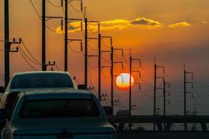 carros e postes elétricos ao pôr do sol foto