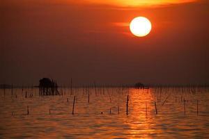 cabana de madeira na água ao pôr do sol foto