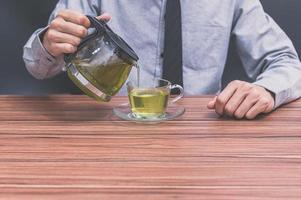 um homem servindo uma xícara de chá