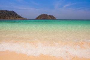 praia tropical com colinas durante o dia