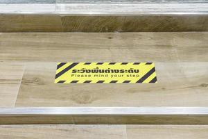 escada com aviso, cuidado com seus passos com a descrição tailandesa