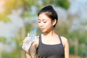 mulher esportiva bebendo água em dia ensolarado foto