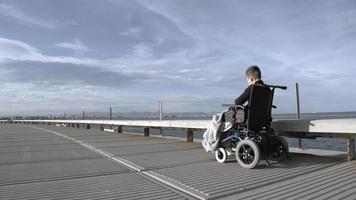 menino em uma cadeira de rodas na praia foto