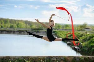 ginasta pulando no ar com uma fita