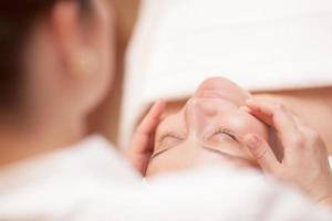 mulher recebendo massagem facial profissional